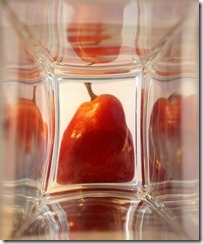 Red ripe pear in the glass box. Bright reflections.